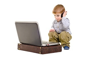 Cute boy speaks on a mobile phone looking at laptop